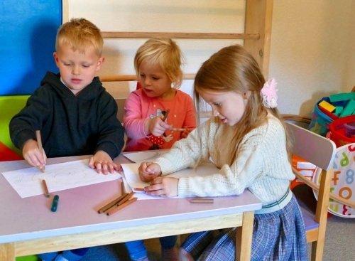 drei Kinder malen am Tisch