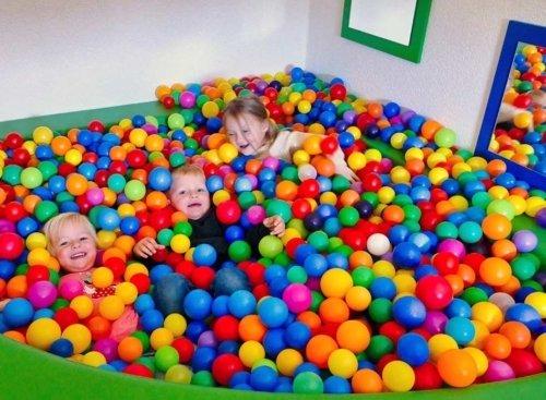drei Kinder toben im Bällebad