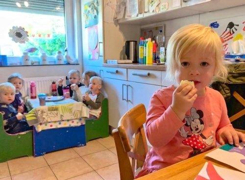sechs Kinder essen gemeinsam Obst in der Küche der Villa Regenwürmchen
