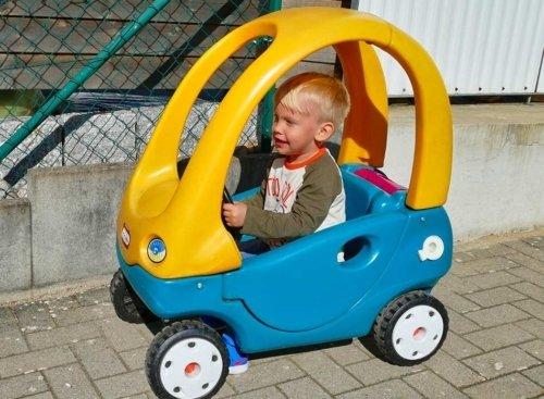 kleine Junge fährt im Tretauto