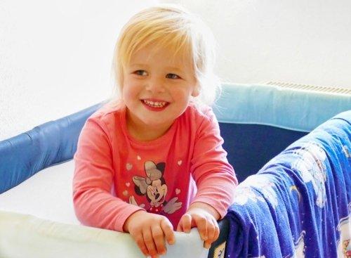 Kind steht lachend im Bett