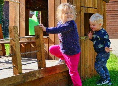 Zwei Kinder klettern auf das Piratenschiff im Garten der Villa Regenwürmchen