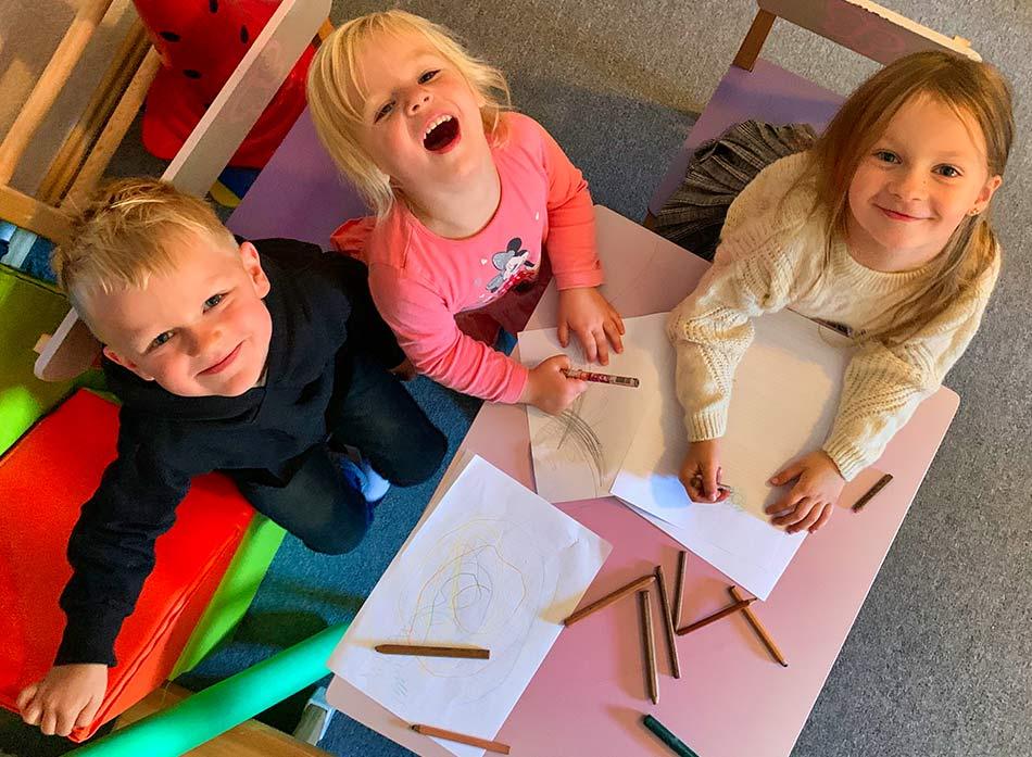 Drei Kinder am Maltisch mit Blick nach oben zur Kamera.