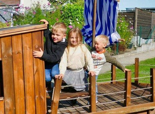Drei Kinder klettern auf dem Piratenschiff im Garten