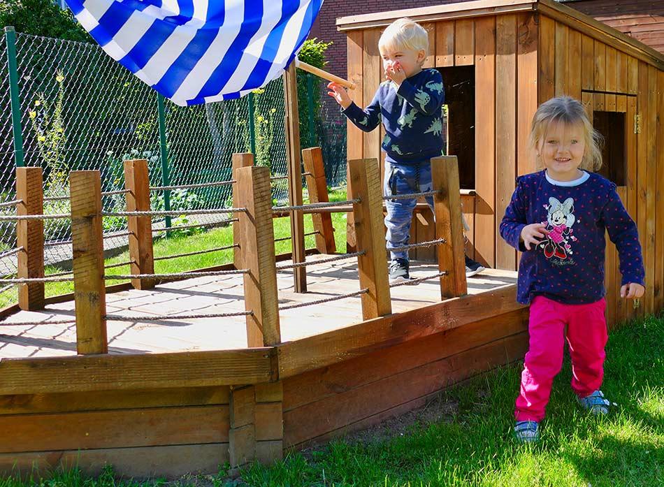 Villa Regenwürmchen - Zwei Kinder spielen im Garten auf dem Holzschiff
