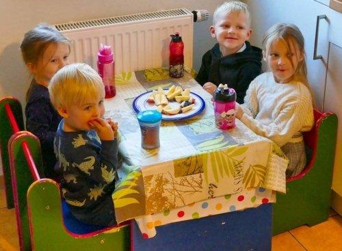 Villa Regenwürmchen - vier Kinder am Küchentisch essen Obst