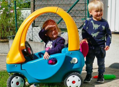 Villa Regenwürmchen - zwei Kinder spielen im Garten mit Tretauto